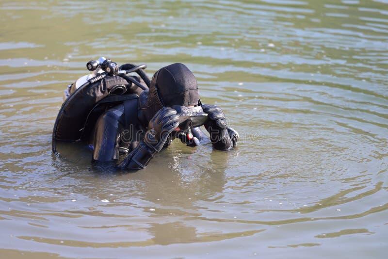 A mulher caucasiano bonita do mergulhador está preparando-se para entrar na água imagens de stock