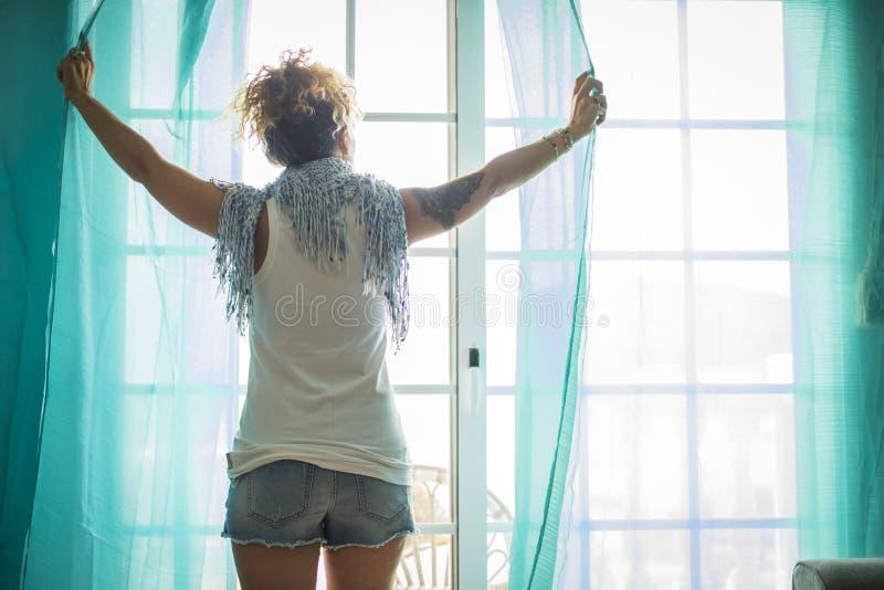 Mulher caucasiano bonita em casa que abre apenas uma janela que move as barracas luz ensolarada do brigh da parte externa estilo  foto de stock royalty free