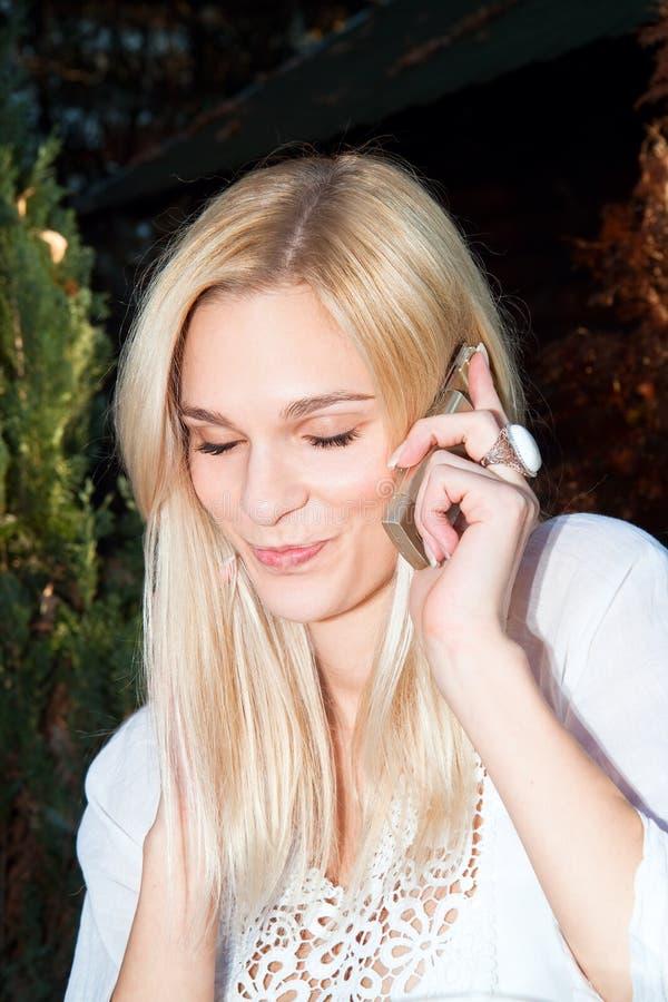 A mulher caucasiano bonita feliz tem um atendimento de telefone foto de stock