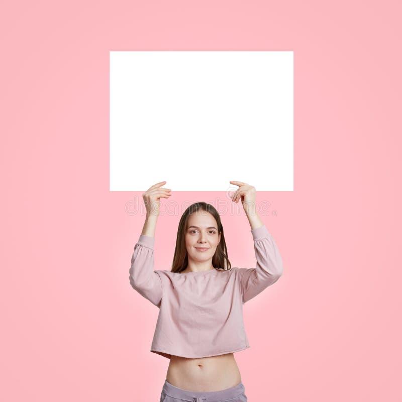 Mulher caucasiano bonita magro na roupa ocasional, cartão branco vazio branco das posses para sua propaganda ou índice relativo à fotografia de stock