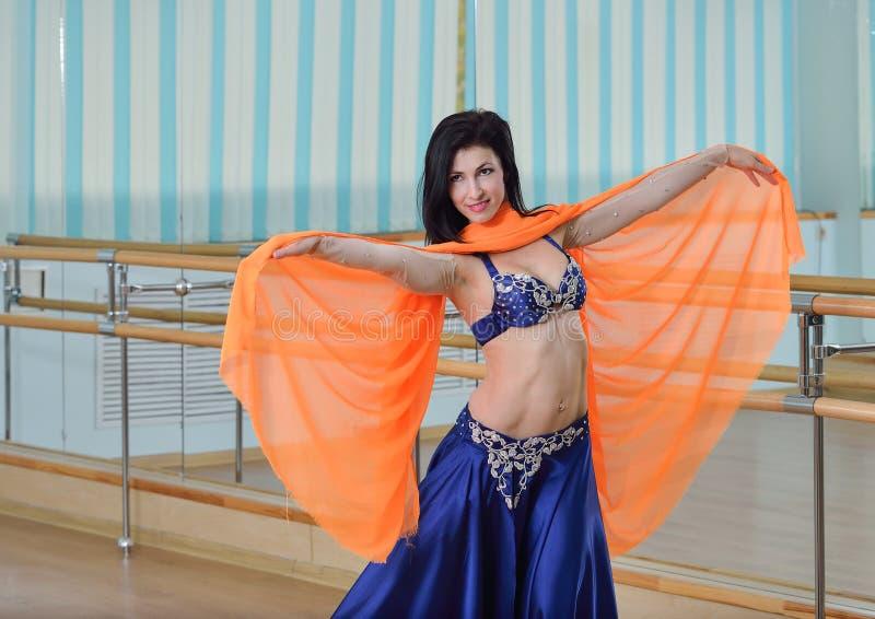 A mulher caucasiano bonita no traje para a dança do ventre está dançando dentro na classe da aptidão fotografia de stock