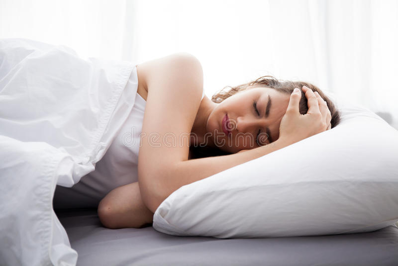 Mulher caucasiano bonita nova na cama que tem a dor de cabeça/insônia/enxaqueca/esforço foto de stock royalty free