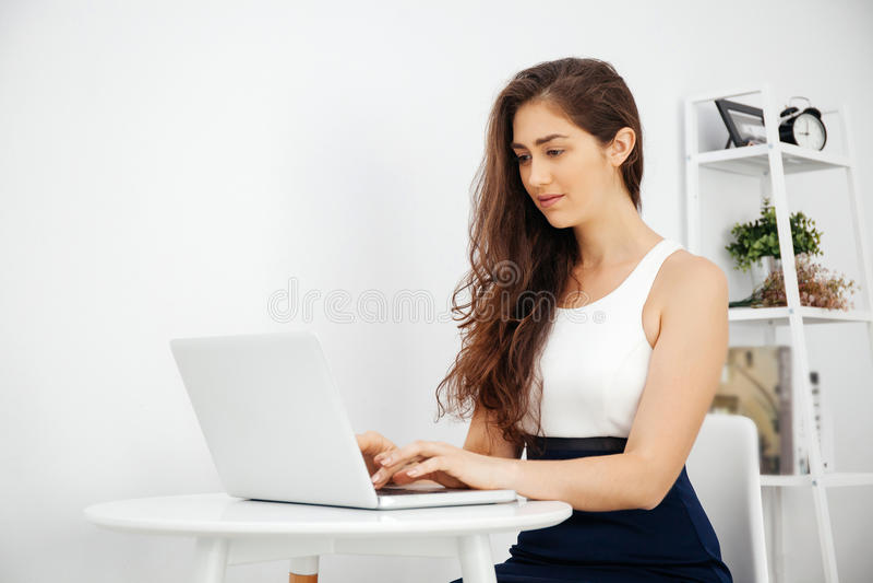 Mulher caucasiano bonita que trabalha no portátil na mesa branca sobre o fundo branco com espaço da cópia imagem de stock