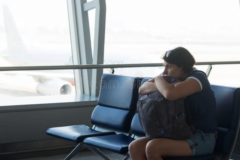 Mulher caucasiano cansado no salão do aeroporto Menina que espera seu voo no terminal de aeroporto, guardando seu saco nas mãos foto de stock