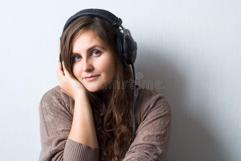 mulher caucasiano com cabelo encaracolado na camiseta com fones de ouvido imagem de stock