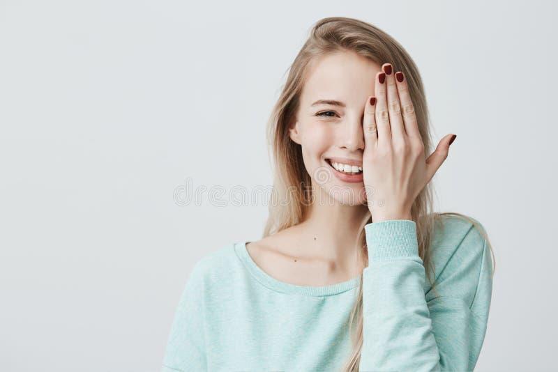 Mulher caucasiano contente com cabelo tingido longo, luz vestindo - camiseta azul, contra o fundo cinzento, fechando seu olho imagens de stock