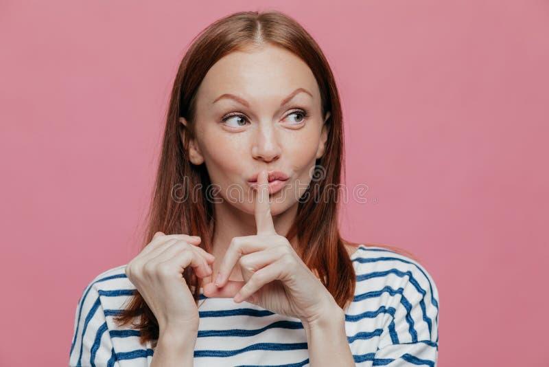 A mulher caucasiano curiosa bonita faz o sinal do silêncio, mantém o indicador sobre a boca, olha secretamente de lado, veste oca fotografia de stock royalty free
