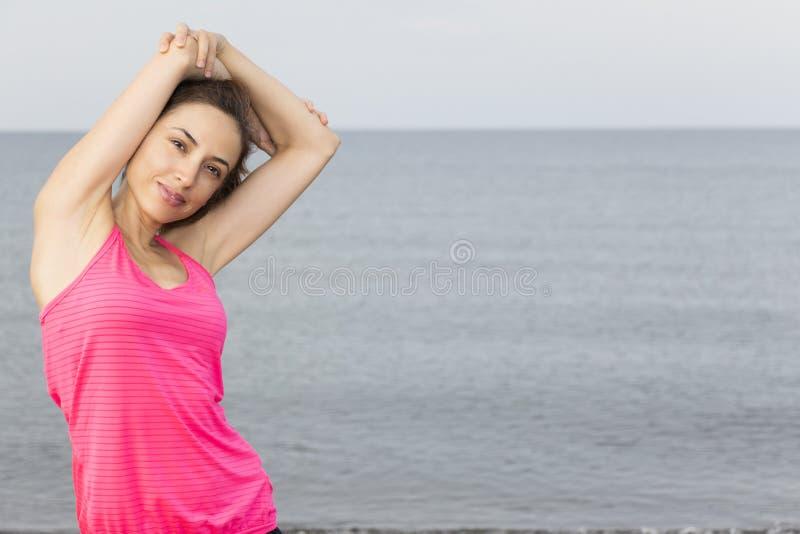 Mulher caucasiano da aptidão que estica seu tríceps foto de stock
