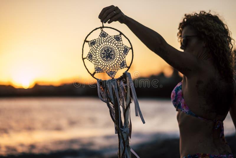 A mulher caucasiano da Idade Média atrativa toma um dreamcatcher feito à mão o tempo exterior do por do sol da praia coloriu a at fotos de stock