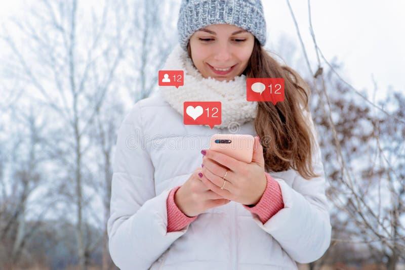A mulher caucasiano da menina guarda o instagram que do telefone os seguidores sociais do ícone do bloger dos meios gostam do con fotos de stock royalty free