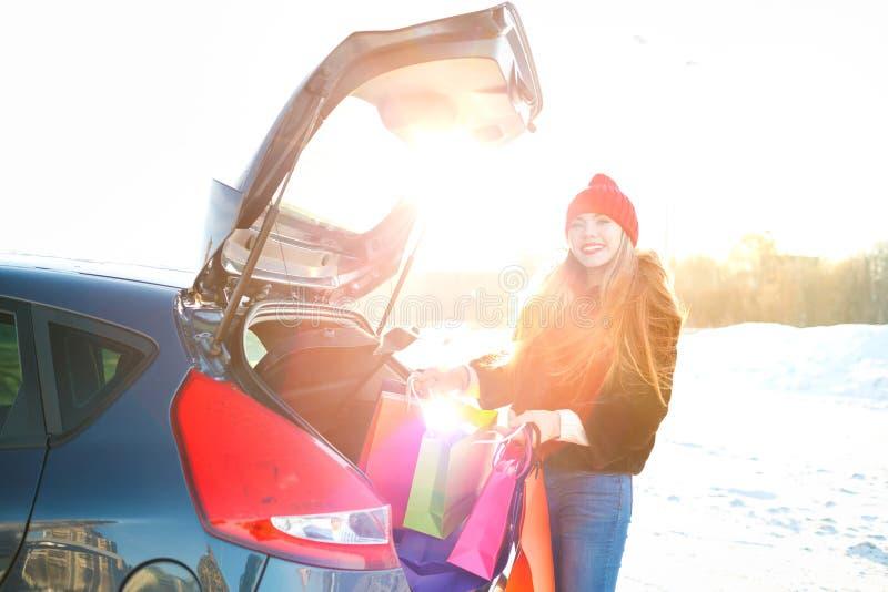 Mulher caucasiano de sorriso que põe seus sacos de compras no carro t fotos de stock