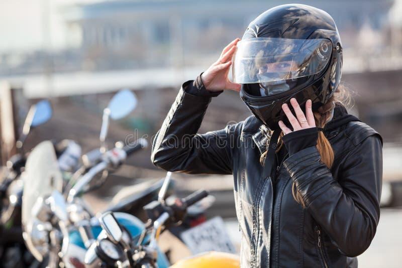 A mulher caucasiano do motociclista ajusta seu capacete da completo-cara, retrato contra bicicletas fundo, espaço da cópia fotos de stock