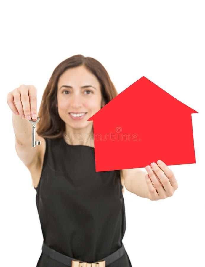 Mulher caucasiano dos bens imobiliários que mostra uma chave para uma casa fotografia de stock