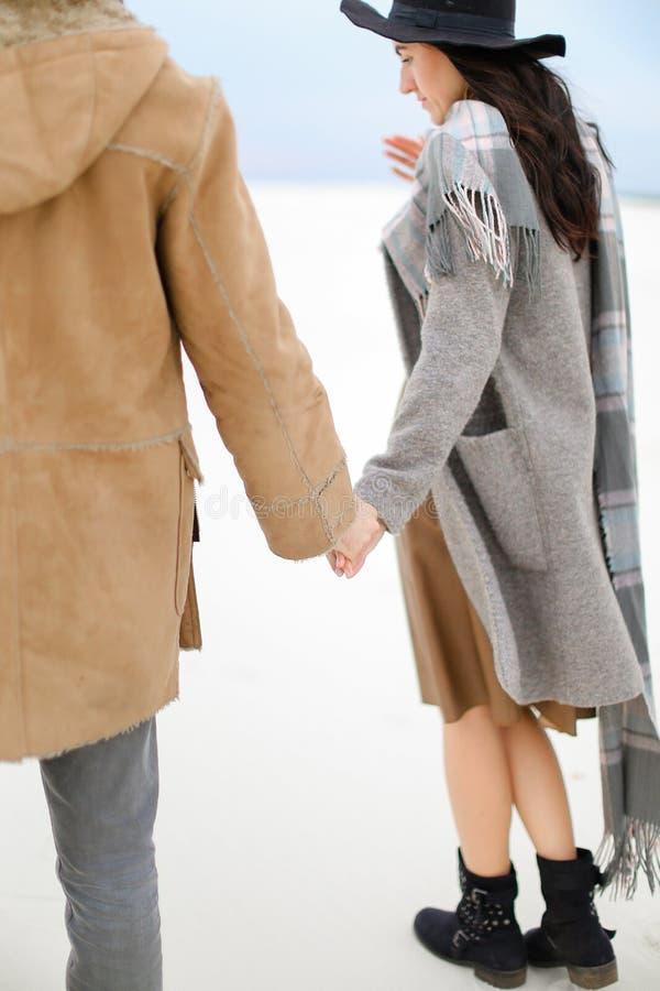 Mulher caucasiano e homem que andam na neve e que guardam as mãos, o revestimento vestindo, o lenço cinzento e o chapéu imagem de stock