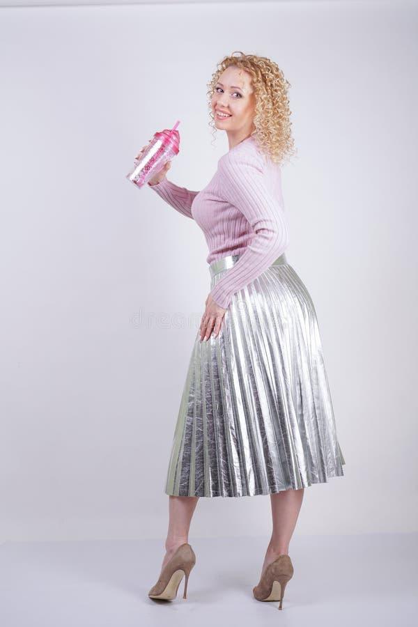 Mulher caucasiano feliz bonita com suportes encaracolados do cabelo louro em uma camiseta feita malha cor-de-rosa fina e em uma S imagens de stock royalty free