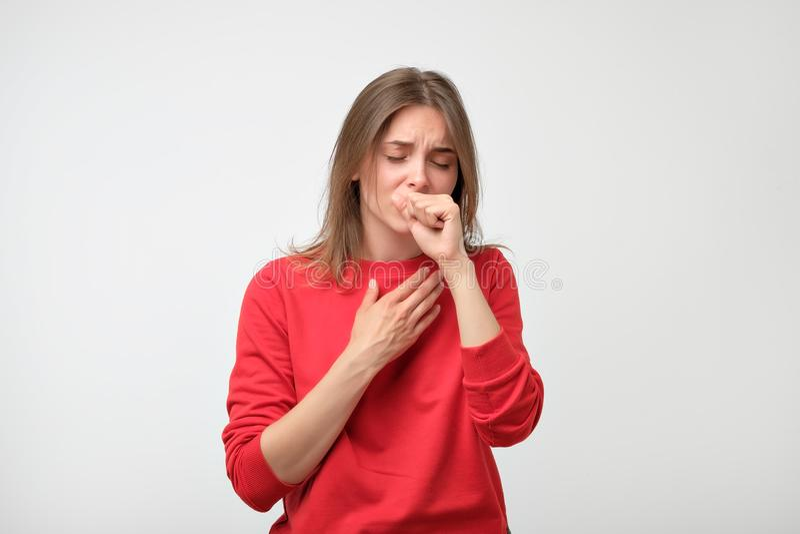 A mulher caucasiano infeliz no pulover vermelho que sofre da garganta causa dor em casa imagens de stock