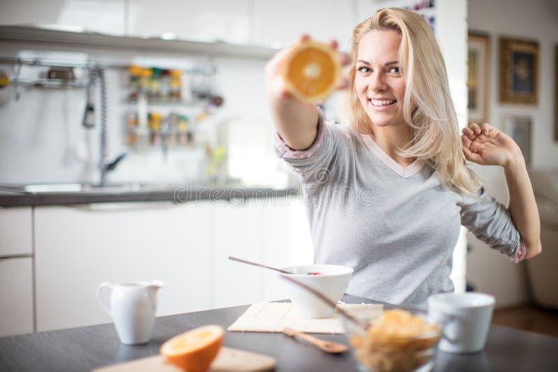 Mulher caucasiano loura bonita que levanta em seu cozinha, ao beber café ou chá e ao comer uma refeição saudável do café da manhã fotografia de stock