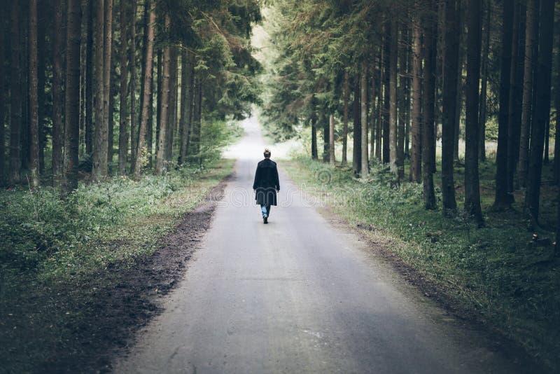 Mulher caucasiano loura nova que anda na estrada através da floresta escura fotografia de stock