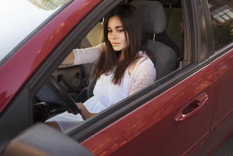 Mulher caucasiano moreno bonita nova que conduz um carro vermelho soma foto de stock