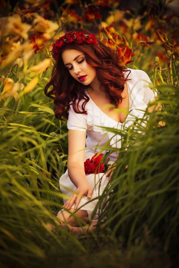 Mulher caucasiano moreno no vestido branco no parque em flores vermelhas e amarelas em um por do sol do verão que guarda as flore imagens de stock royalty free