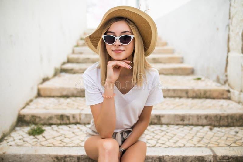 Mulher caucasiano nova bonita que sorri no fundo urbano Menina loura que veste a roupa ocasional na rua imagens de stock