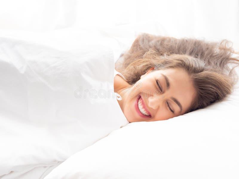 Mulher caucasiano nova feliz que sorri e que dorme na cama com abrandamento e mente tranquilo e calma no fundo branco imagem de stock