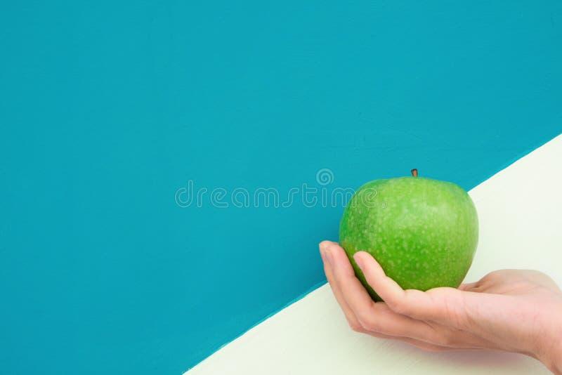 A mulher caucasiano nova guarda Apple orgânico verde disponivel no fundo branco de turquesa de Duotone Dieta saudável das vitamin foto de stock royalty free