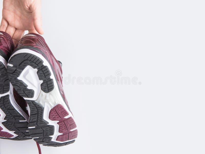 A mulher caucasiano nova guarda pares disponivéis de sapatilhas movimentando-se de formação Fundo branco da parede Motivação dos  fotos de stock