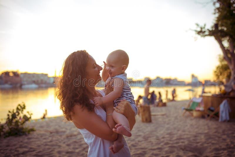 A mulher caucasiano nova, mãe bonita guarda uma criança em seus braços, mamã abraça sua posição de um ano do filho em um Sandy Be fotografia de stock