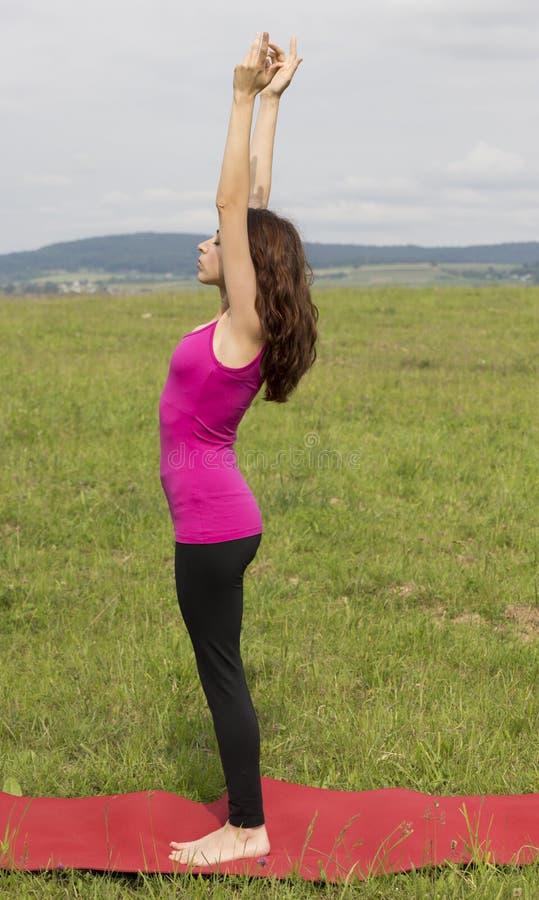 Mulher caucasiano nova na pose ascendente da saudação durante a ioga no natur imagens de stock