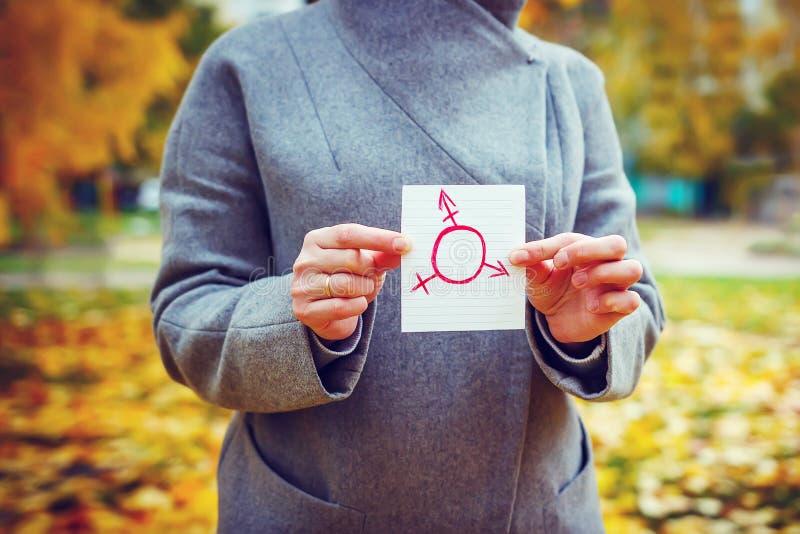 Mulher caucasiano nova no parque do outono que mostra o pedaço de papel com símbolo do transgender tirado nele Conceito do dia do fotos de stock royalty free