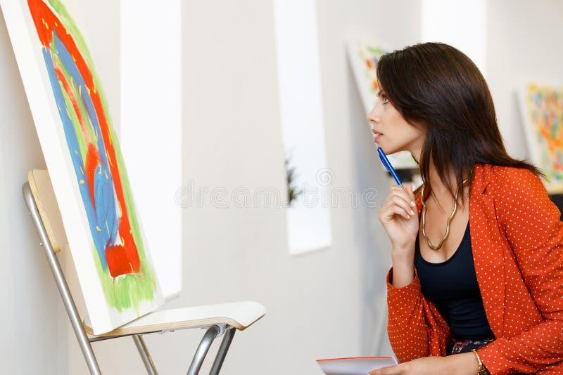 Mulher caucasiano nova que está na parte dianteira da galeria de arte das pinturas imagens de stock royalty free