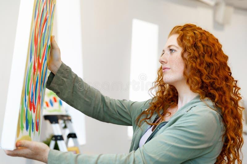 Mulher caucasiano nova que está na parte dianteira da galeria de arte das pinturas imagem de stock royalty free