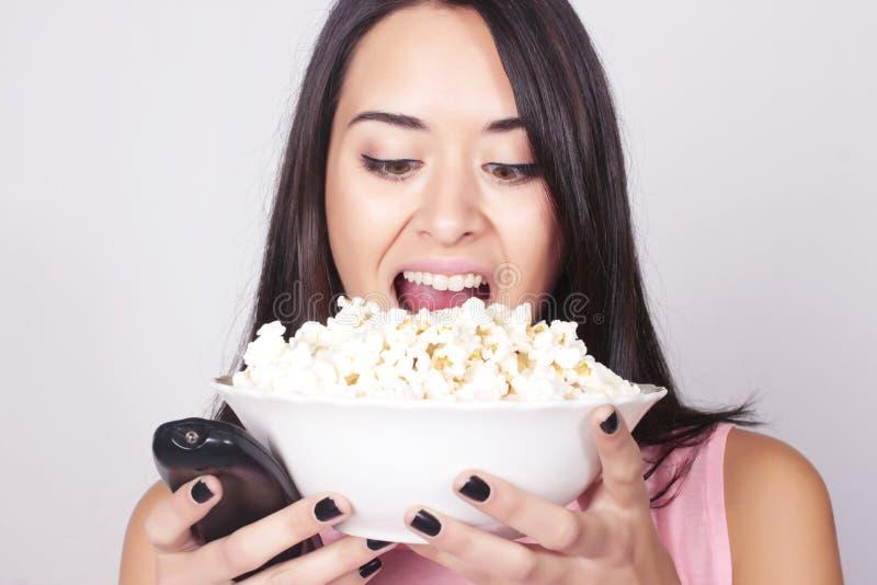 Mulher caucasiano nova que olha um filme/tevê imagens de stock royalty free
