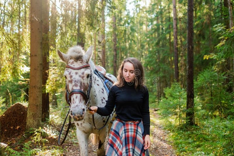 Mulher caucasiano nova que toma de seu cavalo, andando na floresta imagens de stock