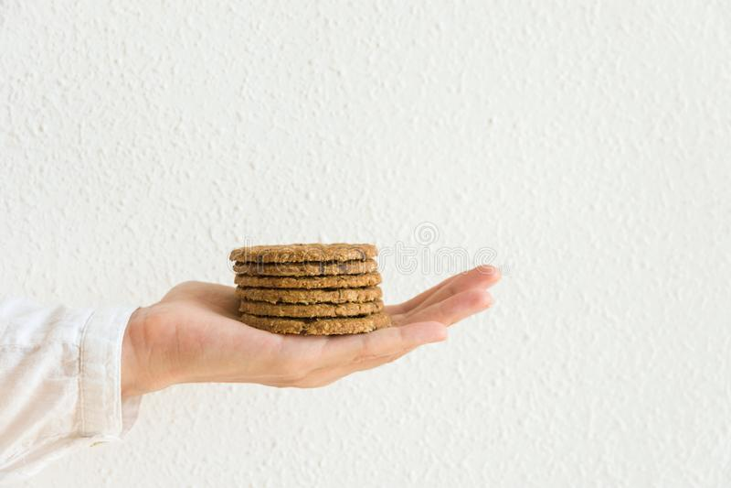 A mulher caucasiano nova realiza na pilha esticada da mão de cookies dos pedaços de chocolate com as porcas do farelo da aveia na fotos de stock royalty free