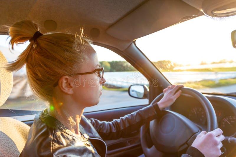 Mulher caucasiano ocasional que conduz o automóvel de passageiros para uma viagem no campo imagem de stock royalty free