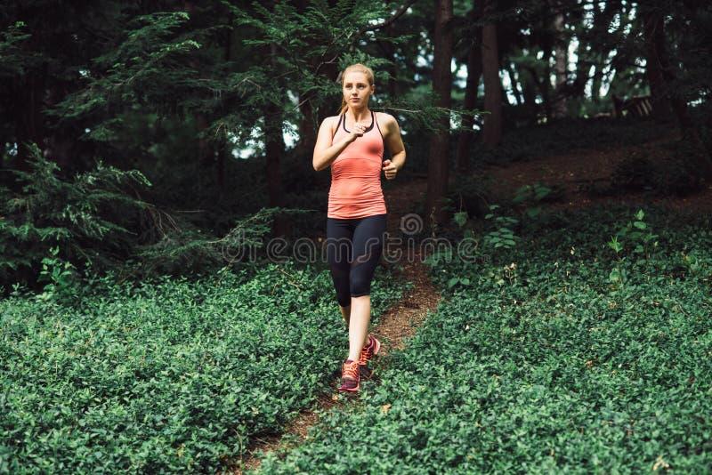 A mulher caucasiano que corre no esporte vestindo da fuga da floresta veste-se imagens de stock