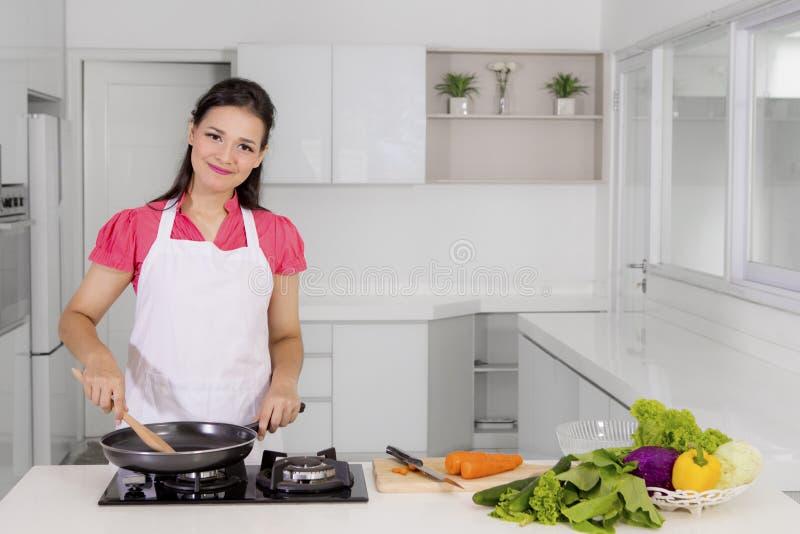 Mulher caucasiano que cozinha vegetais na cozinha imagem de stock royalty free
