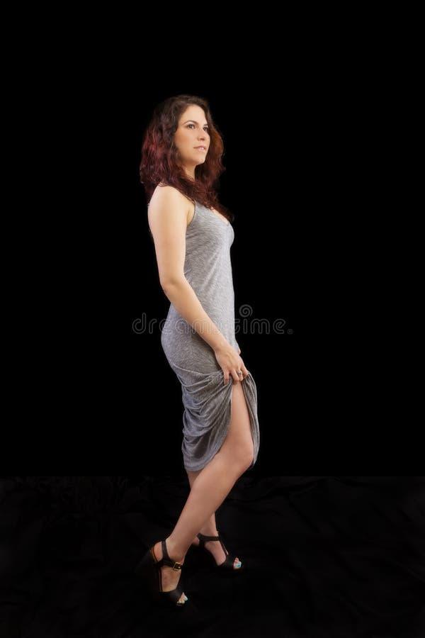 Mulher caucasiano que está Grey Dress Holding Up Hem imagens de stock