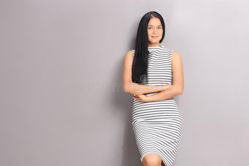 Mulher caucasiano que inclina-se contra uma parede cinzenta imagens de stock