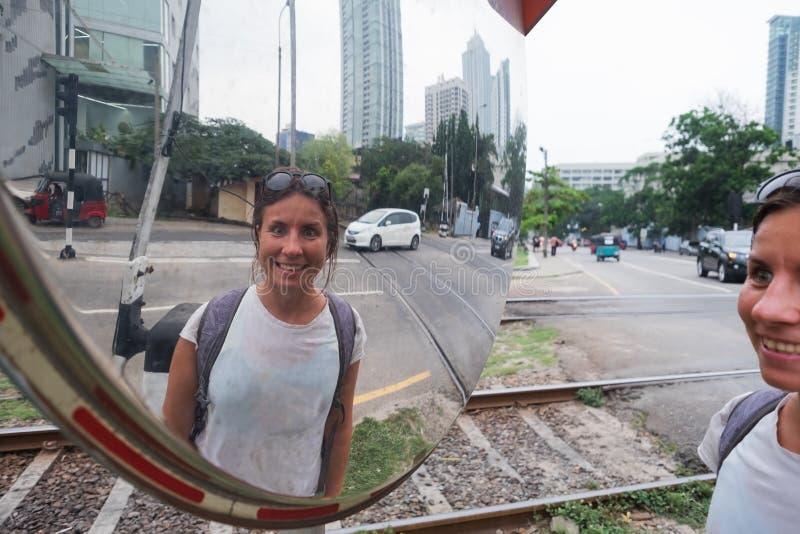 Mulher caucasiano que olha no espelho da estrada fotos de stock