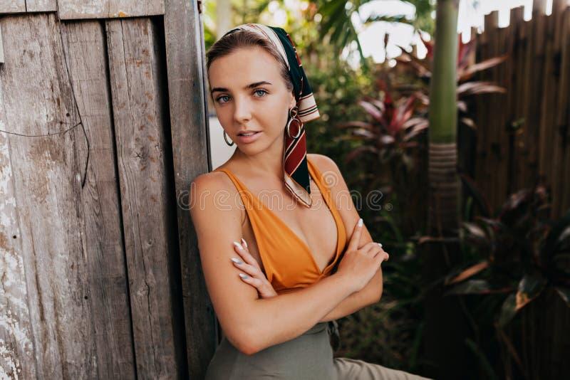 Mulher caucasiano relaxado no xaile na cabeça que levanta ao lado das plantas exóticas Foto da menina europeia sonhadora com pele imagens de stock