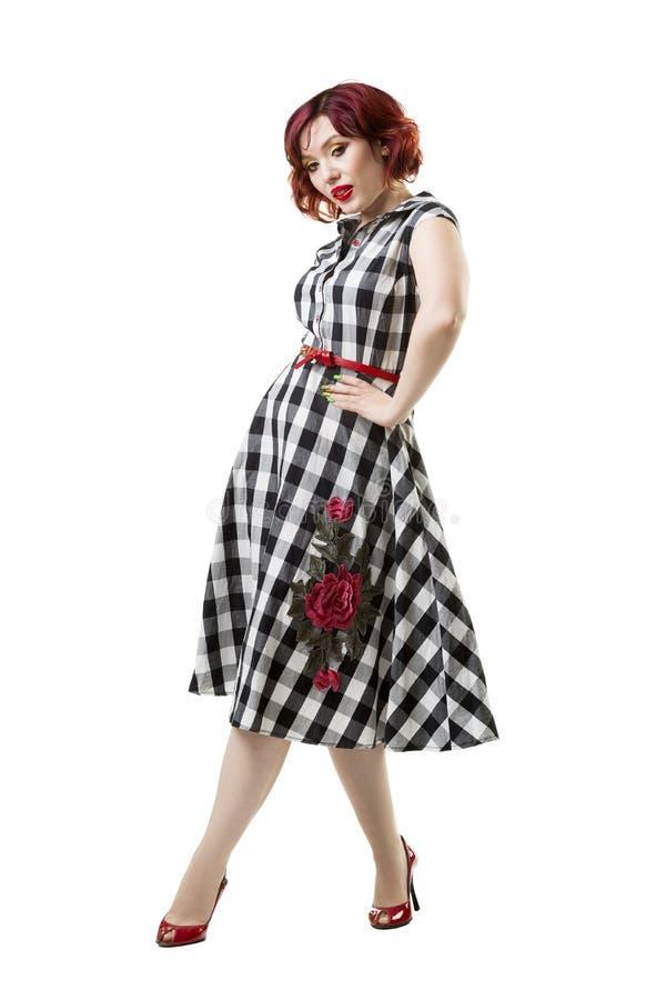 Mulher caucasiano ruivo bonita nova no vestido quadriculado que levanta no estúdio, isolado no fundo branco, composição profissio fotos de stock royalty free