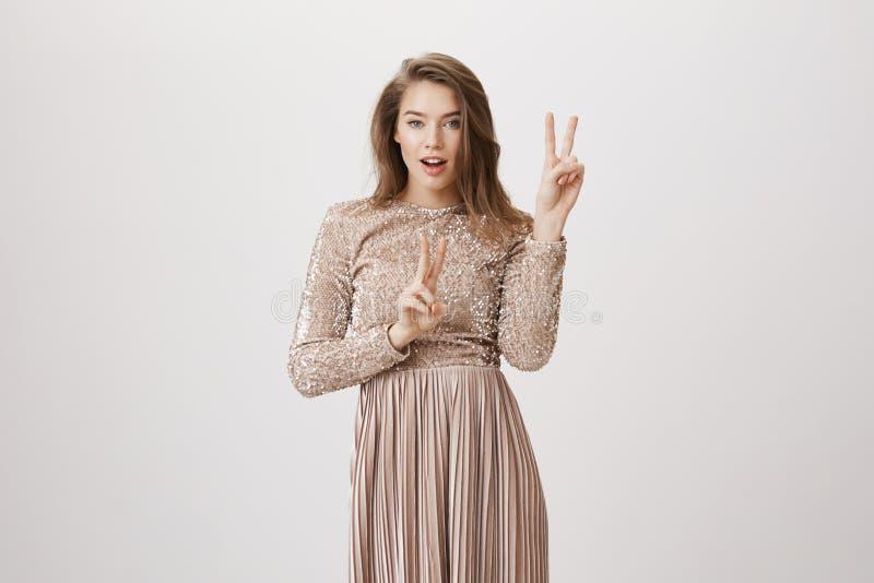A mulher caucasiano sensual encantador no vestido de noite bege de brilho, na vitória da exibição ou na paz gesticula, sentimento foto de stock