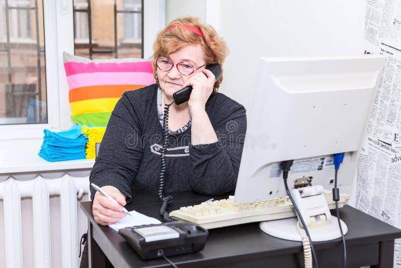 Mulher caucasiano superior que chama o telefone na sala do escritório fotos de stock