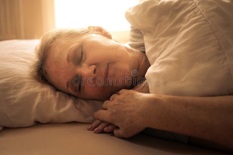 Mulher caucasiano superior que dorme na cama fotografia de stock royalty free