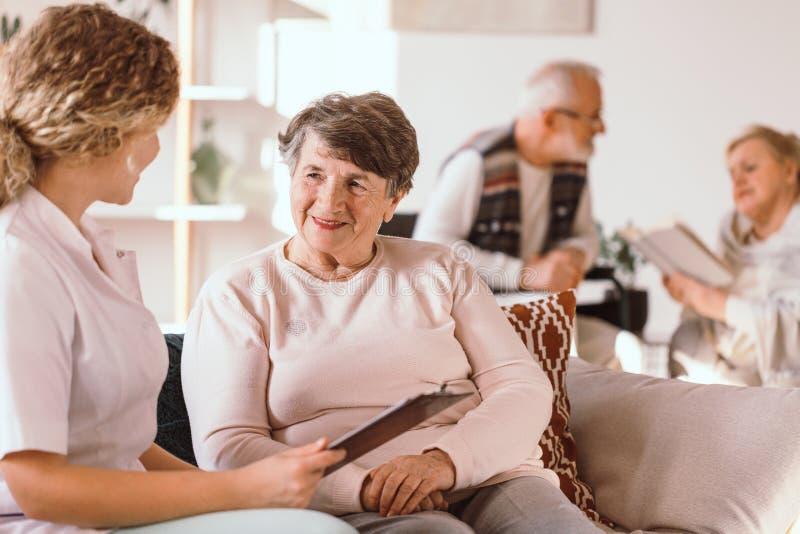 Mulher caucasiano superior que fala com uma enfermeira na facilidade médica imagens de stock royalty free