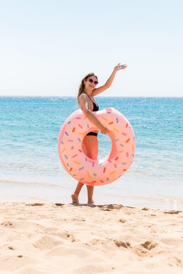 A mulher chama para nadar no mar e acena sua m?o Menina que relaxa no anel inflável na praia F?rias de ver?o e f?rias imagem de stock