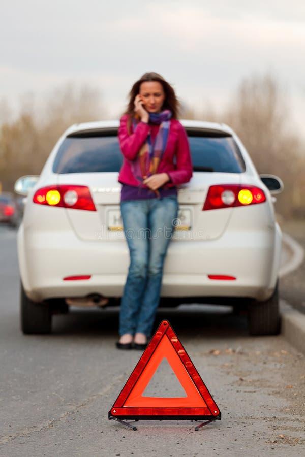 A mulher chama a um serviço que está por um carro branco. imagens de stock royalty free